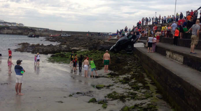 Empty auto rolls down steps into busy Co Clare beach